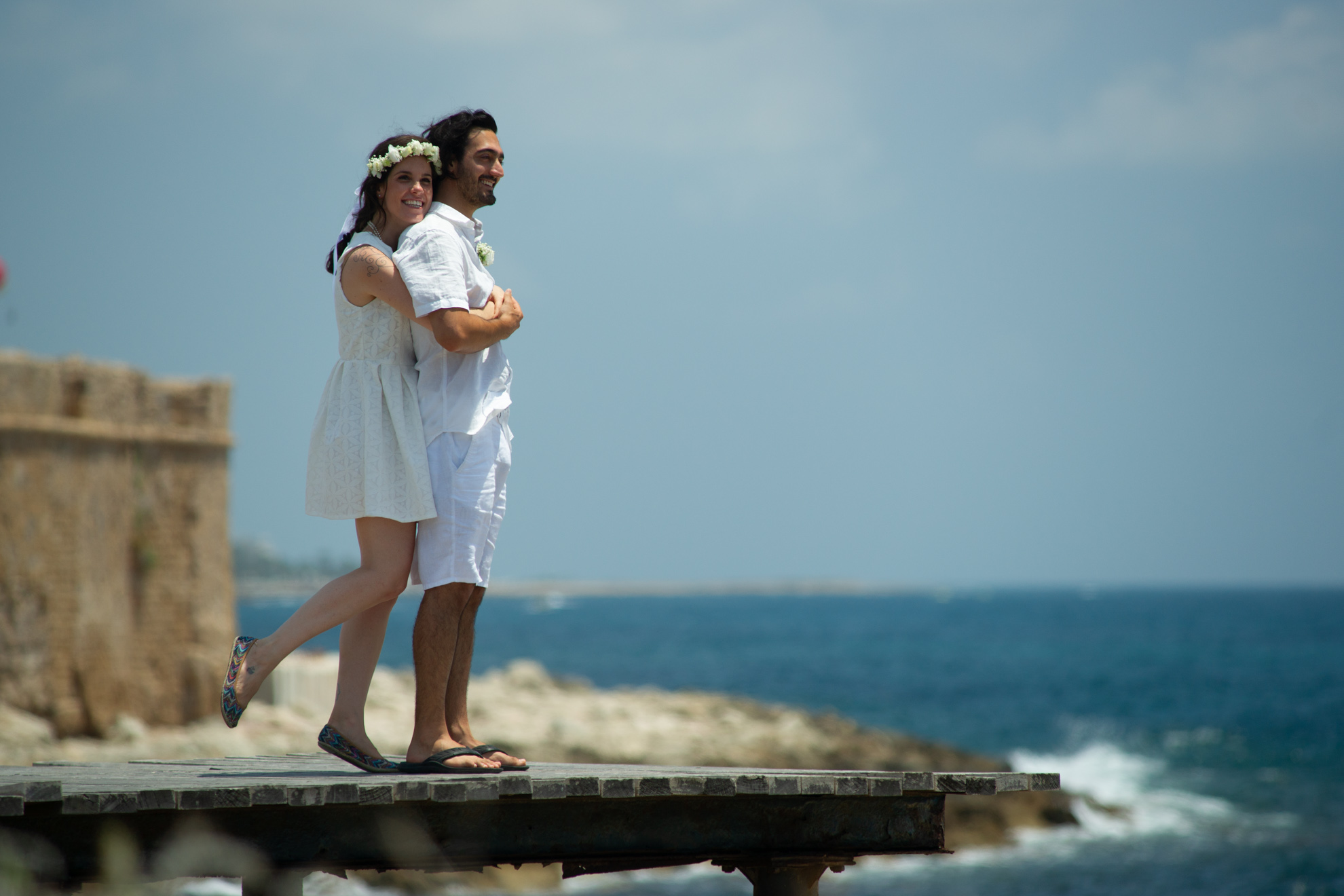 couple on a pier hugging after their wedding in Pafos