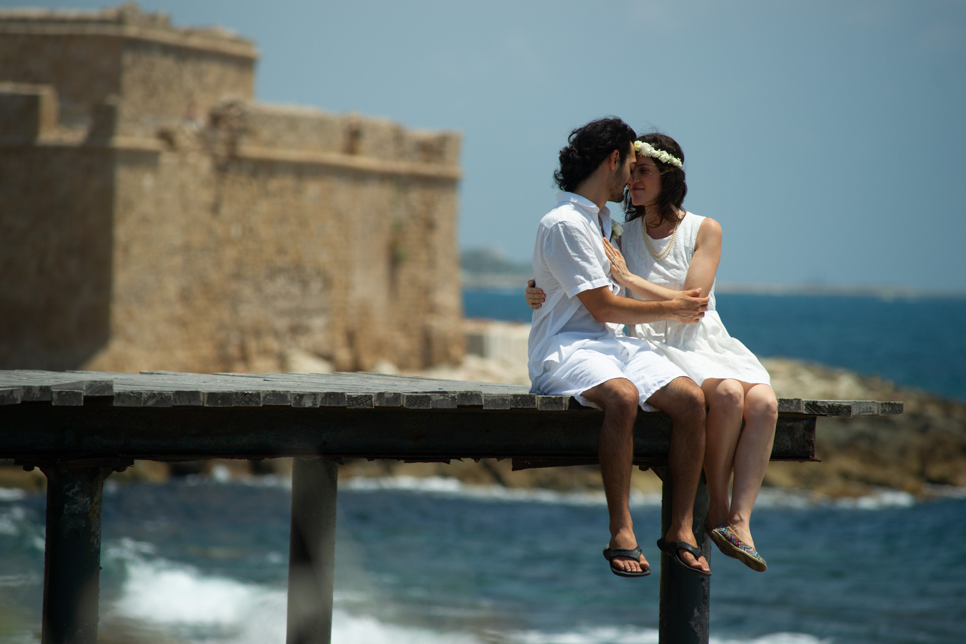 simple wedding dress couple sitting on a pier after their wedding with the Paphos castle on the background