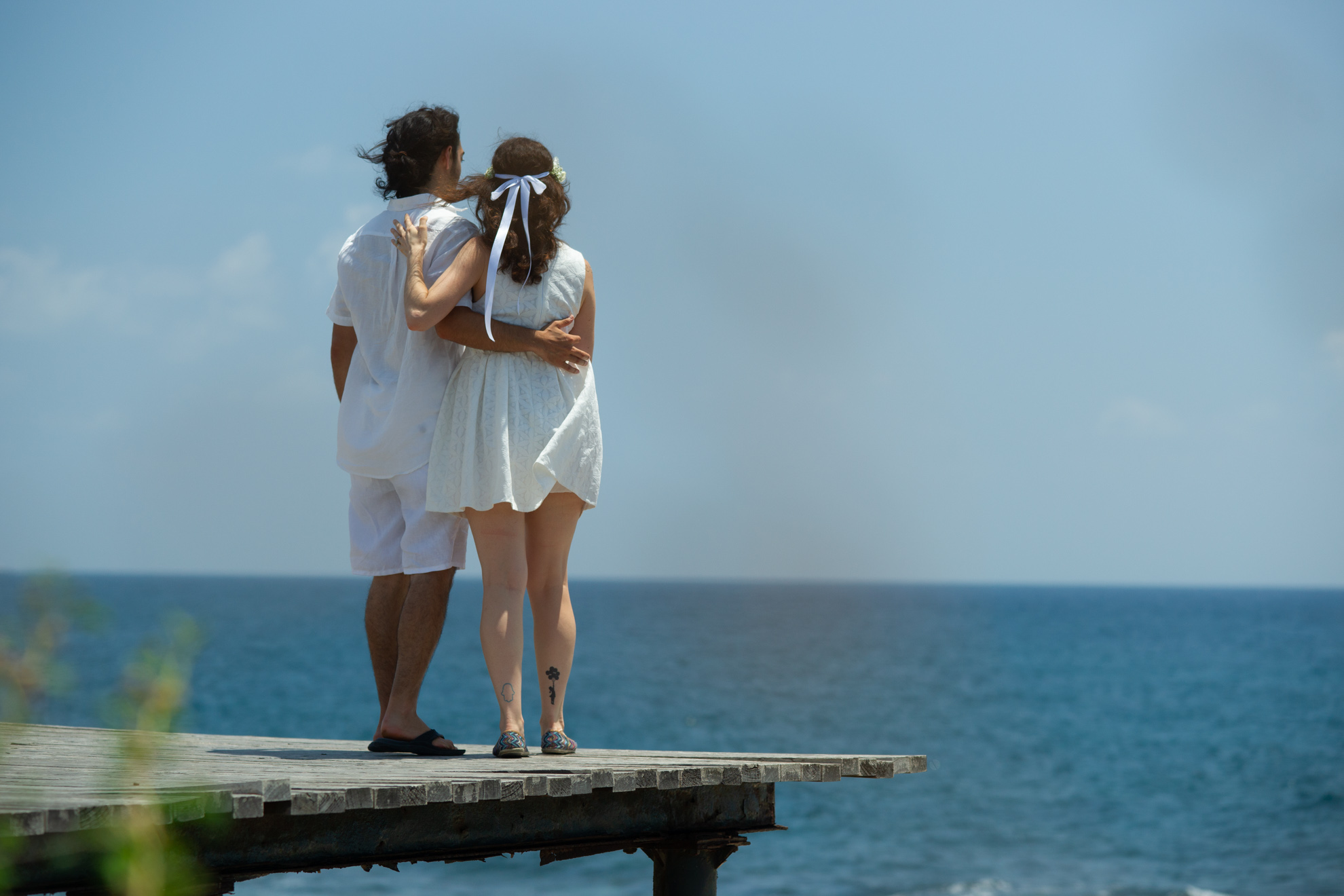 wedding photo of couple holding hands on pier at Pafos seafront looking at the sea